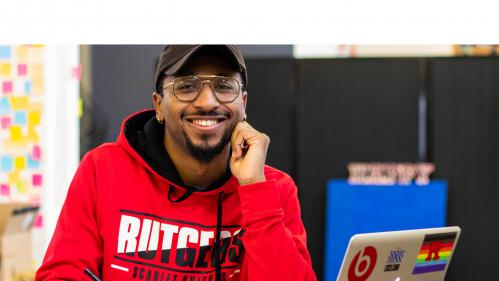 smiling student wearing Rutgers sweatshirt studying on his laptop