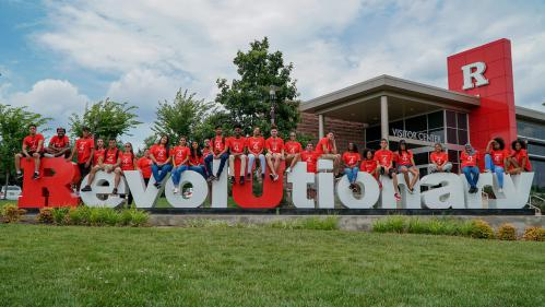 Diverse group of male and female students sitting on large red and white letters that spell out Revolutionary.