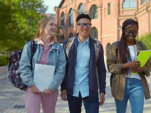 3 students walking on campus talking and smiling. Left to right: young caucasian student, young asian american student, young african american student