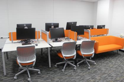 A computer lab with white desk, white chairs with orange padding and an orange couch.